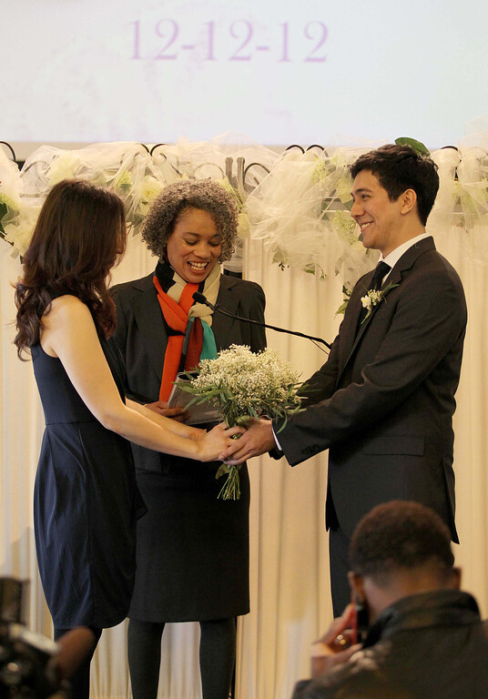. Alameda Mayor Marie Gilmore, center, officiates as Wil Gamboa and Jenna Lee, of Oakland, get married at 12:12 p.m. at City Hall in Alameda, Calif. on Wednesday, Dec. 12, 2012. Two other couples were married at noon at City Hall, and a number of others were married throughout the day. (Jane Tyska/Staff)