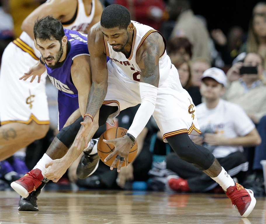 . Sacramento Kings\' Omri Casspi, left, from Israel, and Cleveland Cavaliers\' Kyrie Irving battle for a loose ball in the second half of an NBA basketball game Monday, Feb. 8, 2016, in Cleveland. The Cavaliers won 120-100. (AP Photo/Tony Dejak)