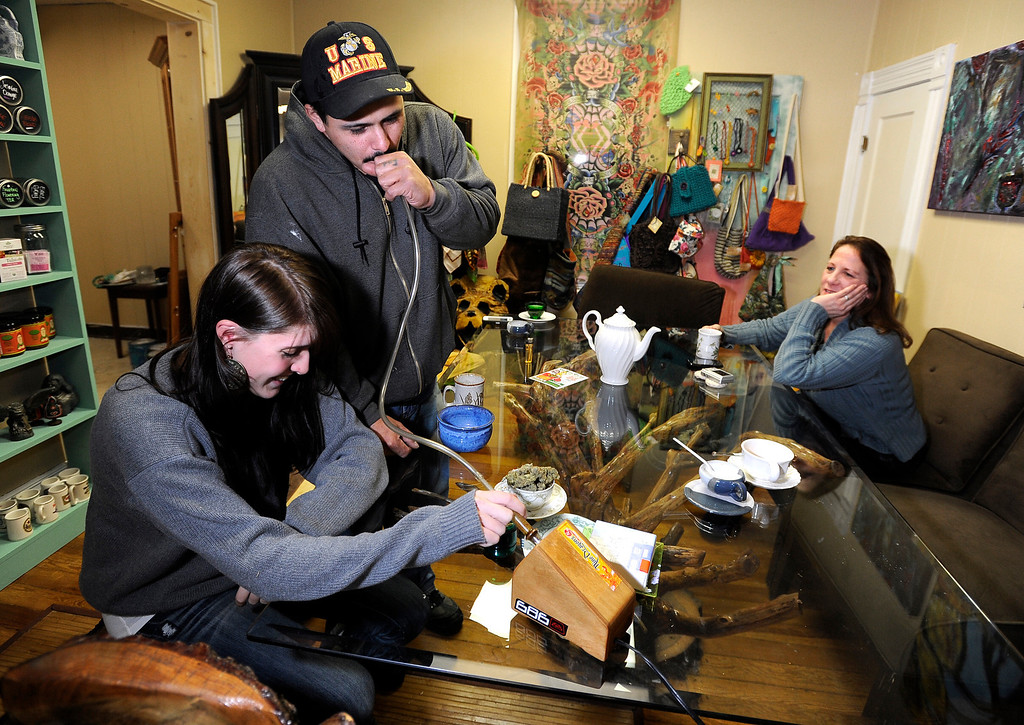 . Rudy Capuchio, of Lafayette, center, takes a hit of marijuana from a vaporizer while smoking with Kyrie Wozab, of Louisville, left, and Heidi Perreria, of Lafayette, right, on Wednesday, Jan. 2, at The Hive Co-Op Cannabis Club in Lafayette. Jeremy Papasso/Boulder Daily Camera