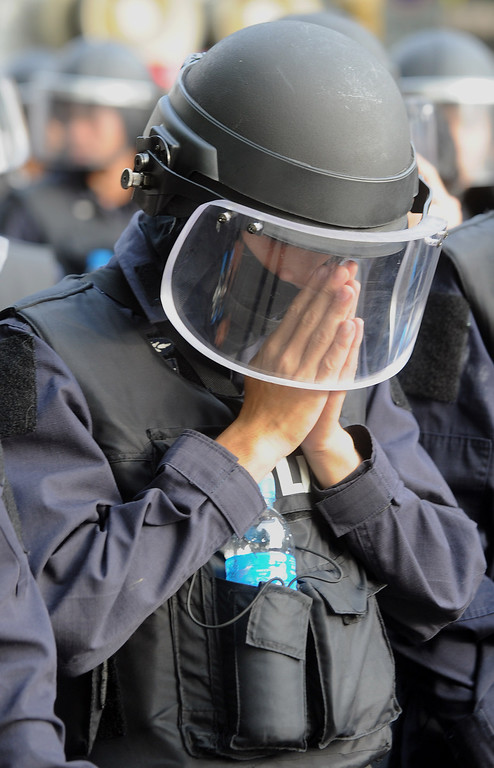 . A Thai policeman offers prayers before marching forward in an attempt to push back anti-government protestors near the Government House in Bangkok on February 18, 2014. TAFP PHOTO / Manjunath Kiran/AFP/Getty Images