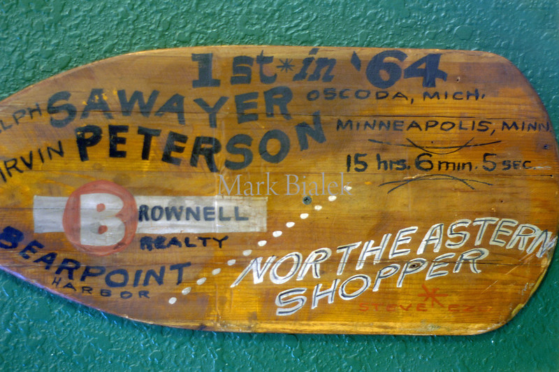 One of several vintage marathon canoe paddles on the wall at the Ausable Inn sports bar and restaurant in Oscoda.  (Photo by Mark Bialek)