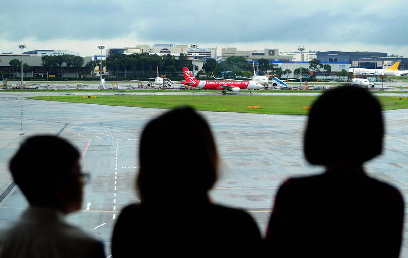 . People watch as an AirAsia plane (C) taxis on the tarmac after landing at terminal 1 at Changi international airport in Singapore on December 29, 2014. Shares in AirAsia, Southeast Asia\'s biggest budget airline, lost more than seven percent in morning trading on December 29 in Kuala Lumpur after one of its jets, AirAsia flight QZ8501, disappeared on December 28 with 162 people on board. MOHD FYROL/AFP/Getty Images