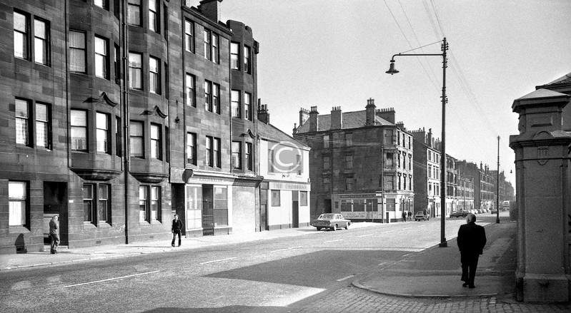 Gallowgate, north side.  Looking east from the Eastern Necropolis entrance. The pubs on either corner of Invernairn St were The Crossbar and The Reekie Linn. Forge cinema hereabouts now.    March 1976
