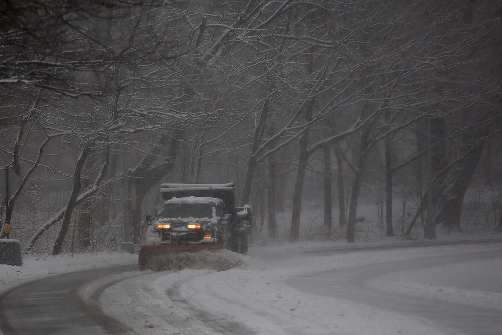 . A plow truck clears a road in a snow-shrouded park on March 8, 2013 in the Brooklyn borough of New York City. As a week-old storm slowly moves out to sea, the New York City area is expecting 1 to 3 inches of snow with more in areas north and west of the city. The storm has caused flight delays at area airports and numerous schools have delayed start times.  (Photo by Spencer Platt/Getty Images)