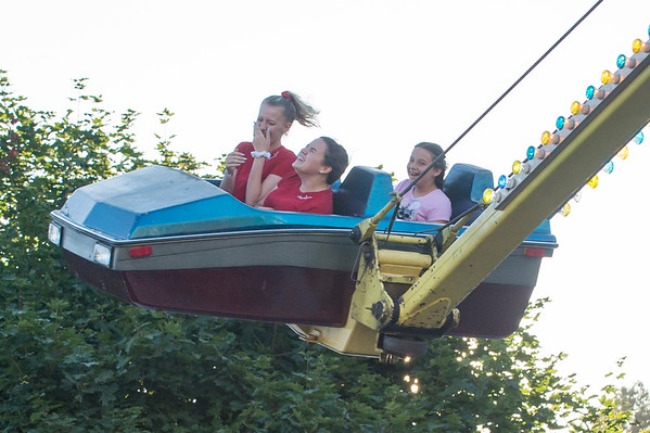 07/12/19 Wesley Bunnell | Staff Claudia Lutynski, L and Julissa Ventura, R, along with a friend ride the Hurricane at the Holy Cross Bazaar on Friday July 12, 2019.