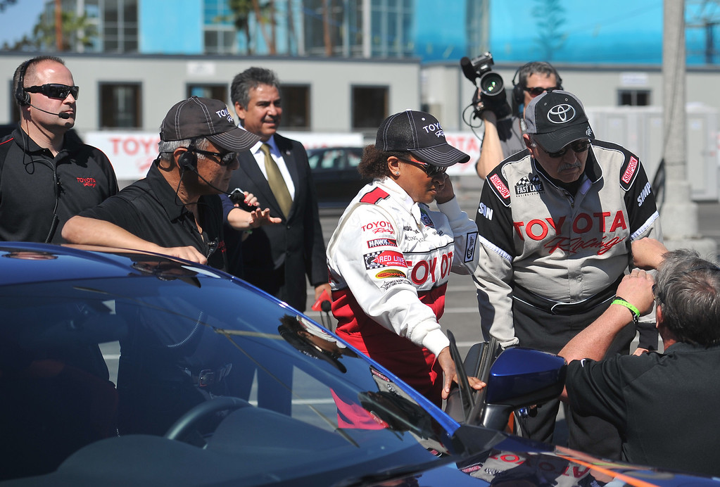 . 4/9/13 - Wanda Sykes gets instructions before entering her car during media day for the 39th Annual Toyota Grand Prix of Long Beach. The celebrity/pro races spent the day practicing on the track, joking with their racing partners and giving interviews. Photo by Brittany Murray / Staff Photographer