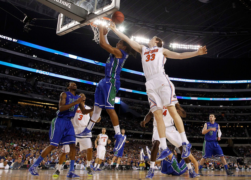 . Florida Gulf Coast Eagles guard Sherwood Brown and Florida Gators forward/center Erik Murphy (33) rebound during the first half in their South Regional NCAA men\'s basketball game in Arlington, Texas March 29, 2013. REUTERS/Jim Young