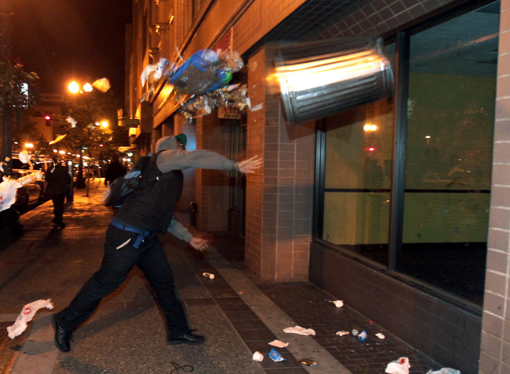. A man throws a trash can at the window of a building during a protest after George Zimmerman was found not guilty in the 2012 shooting death of teenager Trayvon Martin, early Sunday, July 14, 2013, in Oakland, Calif. Protesters angered by the acquittal Zimmerman held largely peaceful demonstrations in three California cities, but broke windows and started small street fires Oakland, police said. (AP Photo/Bay Area News Group, Anda Chu)