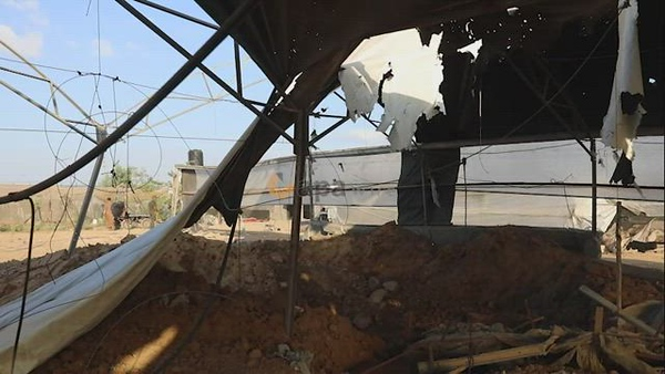 A Palestinian inspects the site of an Israeli airstrike following the Palestinian rocket fire into Israel