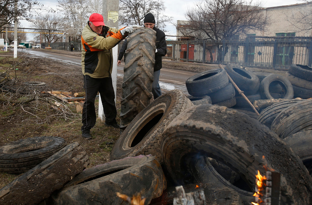 . Pro Russian activists block a road with car tires near the armory Ukrainian army to prevent the export of arms and ammunition in the village of Poraskoveyevka, eastern Ukraine, Thursday, March 20, 2014.  (AP Photo/Sergei Grits)