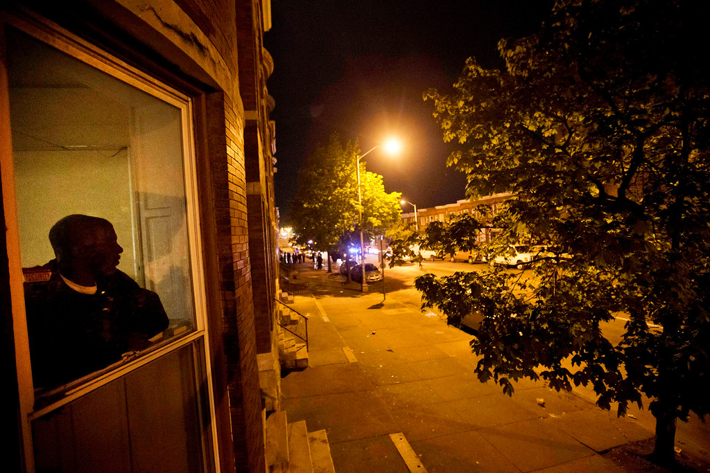 . A resident looks out of a home onto North Avenue, near the scene of Monday\'s riots, after a 10 p.m. curfew went into effect Wednesday, April 29, 2015, in Baltimore. The curfew was imposed after unrest in Baltimore over the death of Freddie Gray while in police custody. (AP Photo/David Goldman)