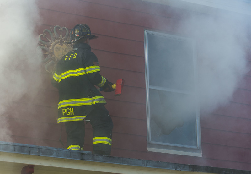 A Fitchburg firefighter prepares to vent a 2nd floor window on Cottage St.