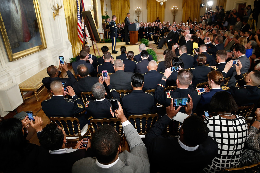 . Members of the audience photograph U.S. President Barack Obama as he speaks during a ceremony to award the Medal of Honor to U.S. Army Sgt. Kyle J. White in the East Room of the White House May 13, 2014 in Washington, DC.  (Photo by Win McNamee/Getty Images)