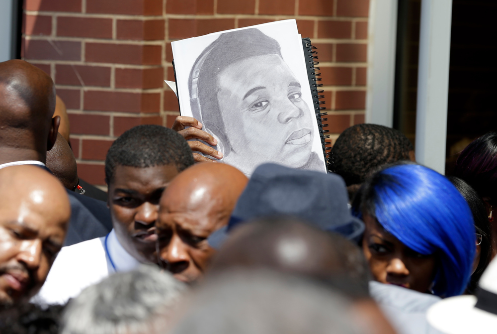 Description of . A sketch showing Michael Brown is seen as people gather outside of Friendly Temple Missionary Baptist Church during the funeral for Michael Brown Monday, Aug. 25, 2014, in St. Louis. Brown, a black 18-year-old who was unarmed, he was shot Aug. 9 by Officer Darren Wilson, who is white. A grand jury is considering evidence in the case and a federal investigation is also underway. (AP Photo/Jeff Roberson)