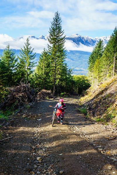 Carolyn Stwertka walks her bike up above Squamish, British Columbia.