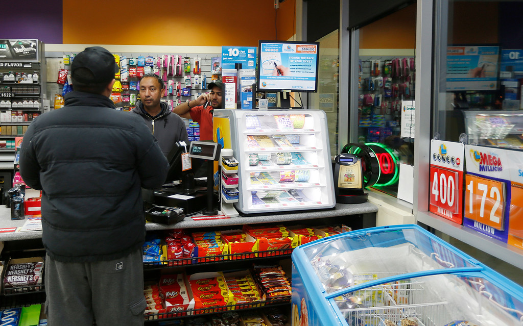 . Employee Gurcharam Sohel, center, helps a customer at the store that sold one a $425 million Powerball ticket at a Dixon Landing gas station in Milpitas, Calif. on Wednesday, Feb. 19, 2014. (Josie Lepe/Bay Area News Group)