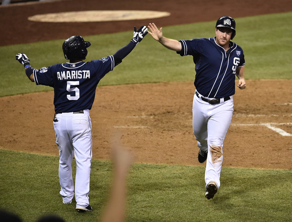 . SAN DIEGO, CA - SEPTEMBER 23:  Jedd Gyorko #9 of the San Diego Padres, right, is congratulated by Alexi Amarista #5 after scoring during the sixth inning of a baseball game against the Colorado Rockies at Petco Park September, 23, 2014 in San Diego, California.  (Photo by Denis Poroy/Getty Images)