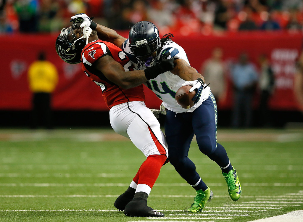 . Marshawn Lynch #24 of the Seattle Seahawks stiff arms William Moore #25 of the Atlanta Falcons at Georgia Dome on November 10, 2013 in Atlanta, Georgia.  (Photo by Kevin C. Cox/Getty Images)