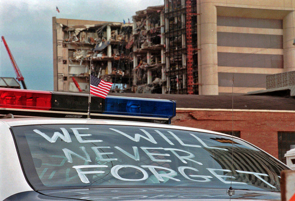 ". FILE - In this April 24, 1995 file photo, an Oklahoma City police car decorated with the words, ""We will never forget,\"" and a small American flag sits near the Alfred P. Murrah Federal Building in Oklahoma City. The blast killed 168 people - including 19 children - injured hundreds more and caused hundreds of millions of dollars in damage to structures and vehicles in the downtown area. (AP Photo/Rick Bowmer, File)"