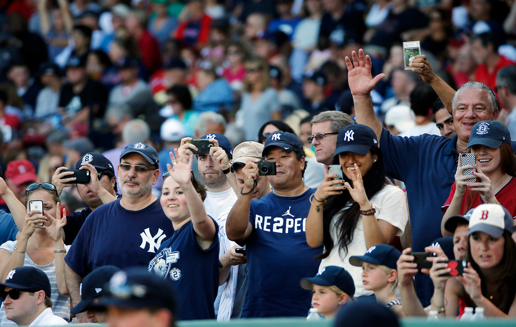 . Fans waves and take photos of New York Yankees designated hitter Derek Jeter in the dugout as the Yankees player the Boston Red Sox in a baseball game Sunday, Sept. 28, 2014, in Boston. It is the last baseball game of Jeter\'s career. (AP Photo/Elise Amendola)