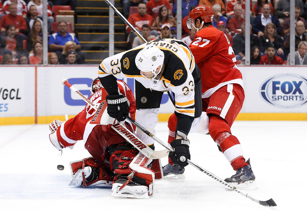 . Boston Bruins defenseman Zdeno Chara (33) is dumped by Detroit Red Wings defenseman Kyle Quincey (27) as goalie Jimmy Howard (35) deflects the puck in the third period of an NHL hockey game in Detroit, Wednesday, Oct. 15, 2014. (AP Photo/Paul Sancya)