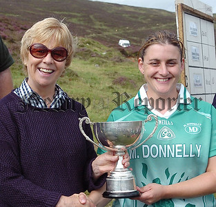 Liz Howard  President of Ladies Camogie presenting  Mary Henry of Westmeath with the  Camogie Poc Fada All Ireland  Cup on the Cooley Mountains