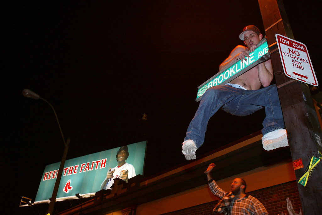 . An unidentified man climbs a signpost outside Fenway Park in Boston after the Boston Red Sox swept the St. Louis Cardinals to win the World Series Wednesday, Oct. 27, 2004.  (AP Photo/Daniel Bersak)