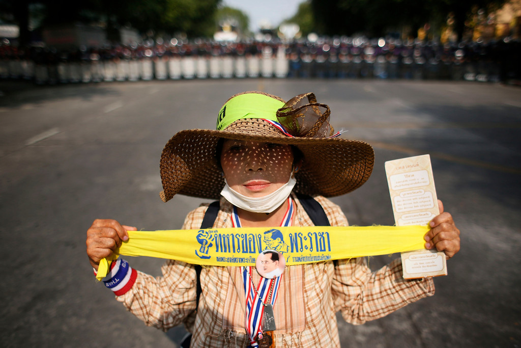 ". A lone anti-government protester holds a ribbon that reads ""king\'s soldier\"" in front of a line of riot police during a stand-off in Bangkok, Thailand, Tuesday, Feb. 18, 2014. (AP Photo/Wally Santana)"