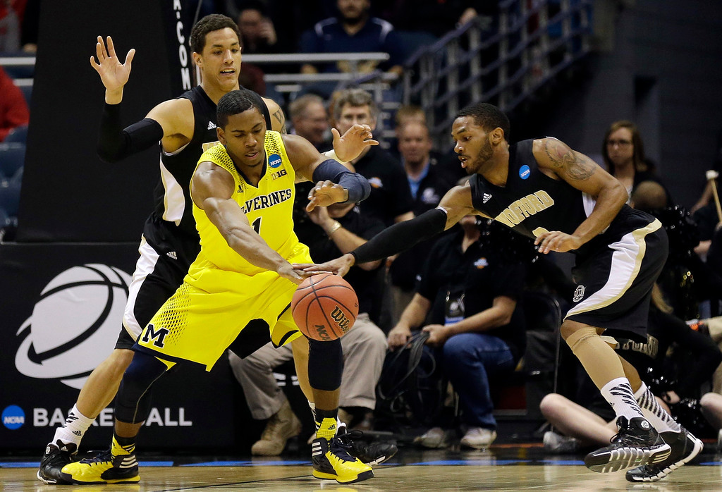 . Wofford guard Karl Cochran, right, tries to steal a ball from Michigan forward Glenn Robinson III during the first half of a second round NCAA college basketball tournament game Thursday, March 20, 2014, in Milwaukee. (AP Photo/Jeffrey Phelps)