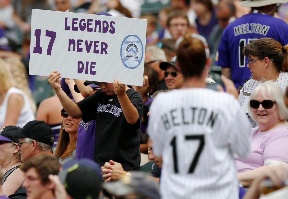 . Fans hold up placards for retired Colorado Rockies first baseman Todd Helton before his number was retired in a ceremony before the Rockies baseball game with the Cincinnati Reds in Denver on Sunday, Aug. 17, 2014. (AP Photo/David Zalubowski)