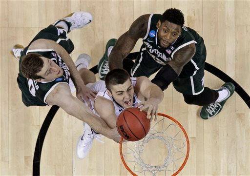 . Virginia\'s Mike Tobey, center, dunks as Michigan State\'s Matt Costello, left, and Branden Dawson, right, defend during the second half of an NCAA tournament college basketball game in the Round of 32 in Charlotte, N.C., Sunday, March 22, 2015. Michigan State won 60-54. (AP Photo/Gerald Herbert)