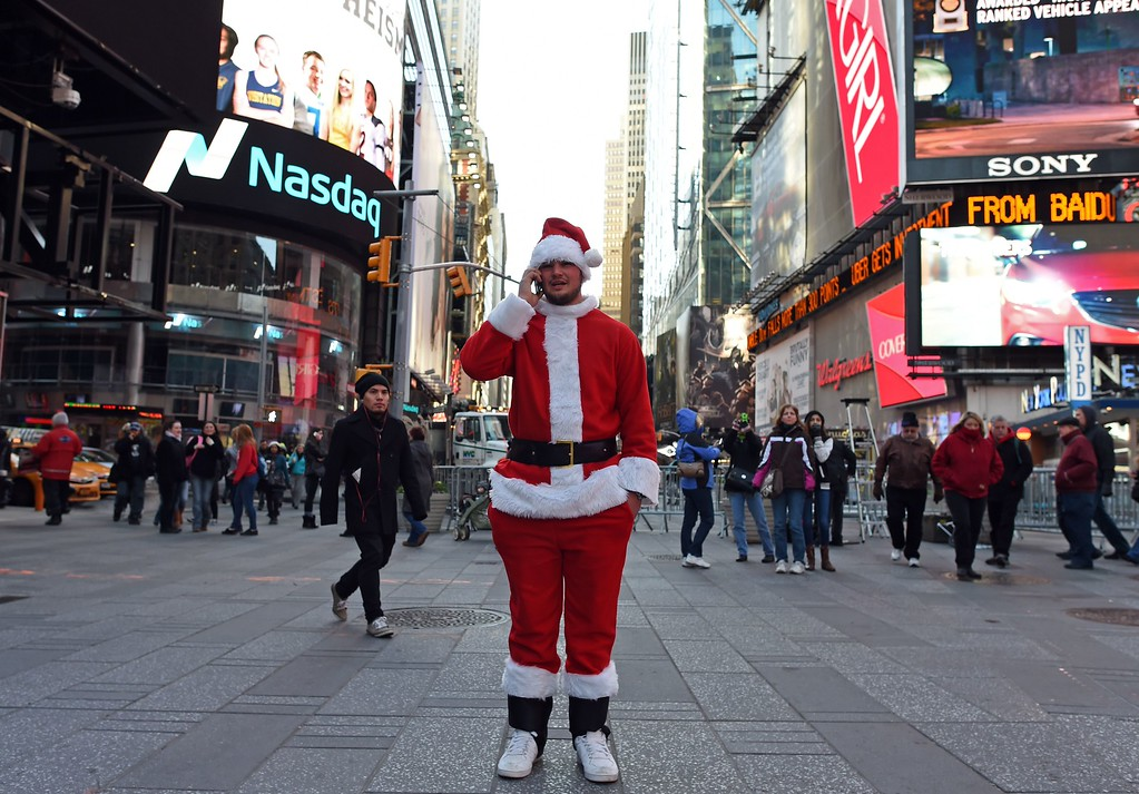 . Santa makes a phone call in Times Square as hundreds of Santas gather for the annual Santacon festivities on December 13, 2014 in New York. AFP PHOTO/DON  EMMERT/AFP/Getty Images
