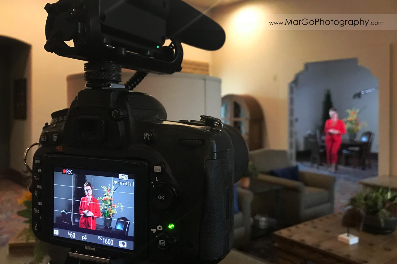 behind the scenes of indoor filming woman speaker in red suit - focus on camera
