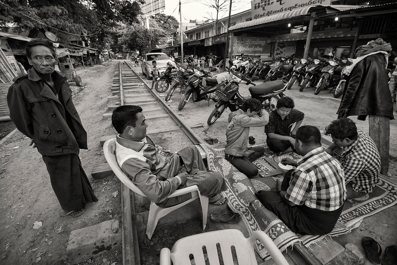 Friends playing a board game on the rail tracks.  Meiktila, Myanmar, 2017.