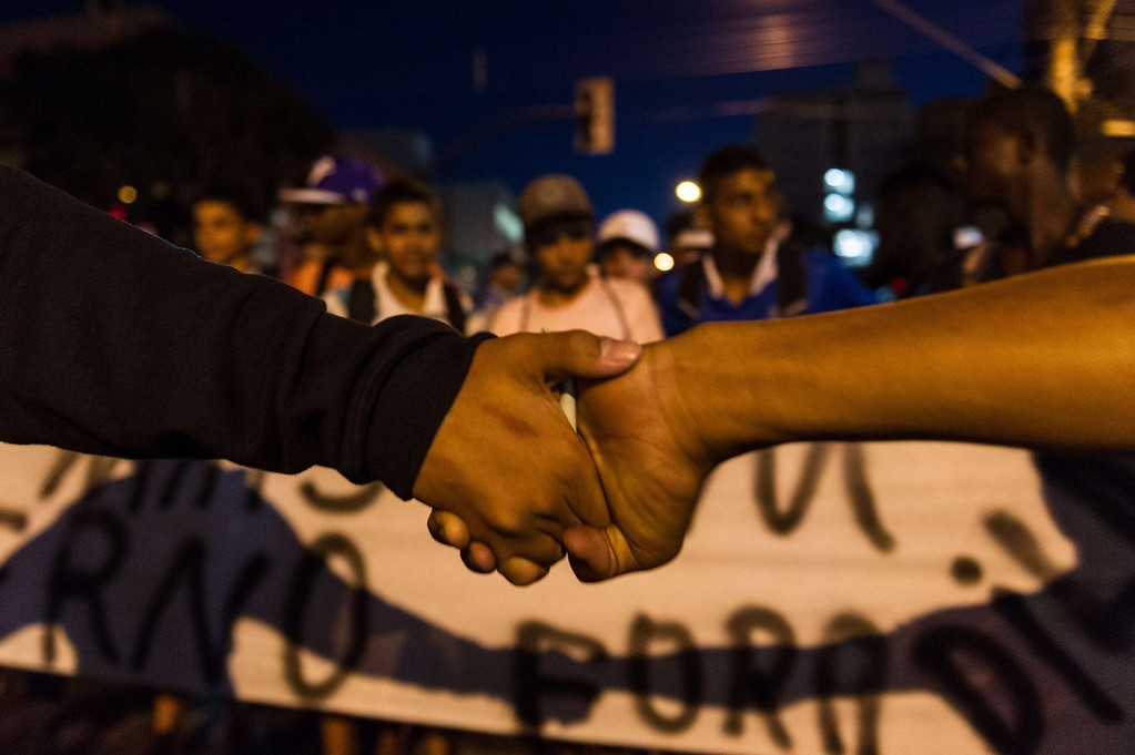 . Men hold their hands during a demonstration in Belo Horizonte, Brazil, on June 21, 2013. AFP PHOTO / YASUYOSHI  CHIBA/AFP/Getty Images