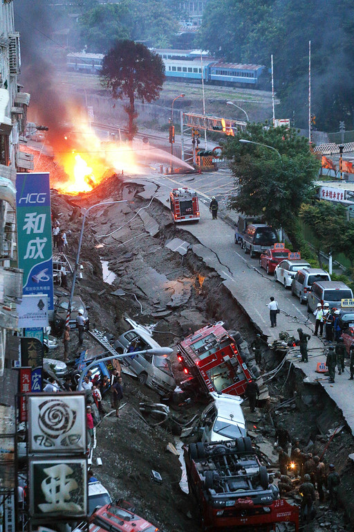 . Vehicles are left lie in a destroyed street as part of the street is burning with flame following multiple explosions from an underground gas leak in Kaohsiung, Taiwan, early Friday, Aug. 1, 2014. A massive gas leakage early Friday caused five explosions that killed scores of people and injured over 200 in the southern Taiwan port city of Kaohsiung. (AP Photo)