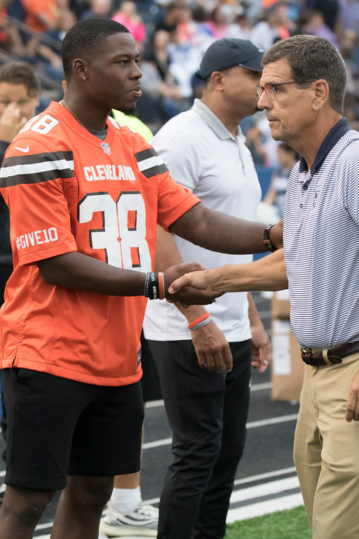 . Jen Forbus - The Morning Journal<br> Coach Dave McFarland welcomes Cleveland Browns defensive back T.J. Carrie to the Titans sideline for Lorain\'s game against Ottawa St. Joseph on Sept. 14.