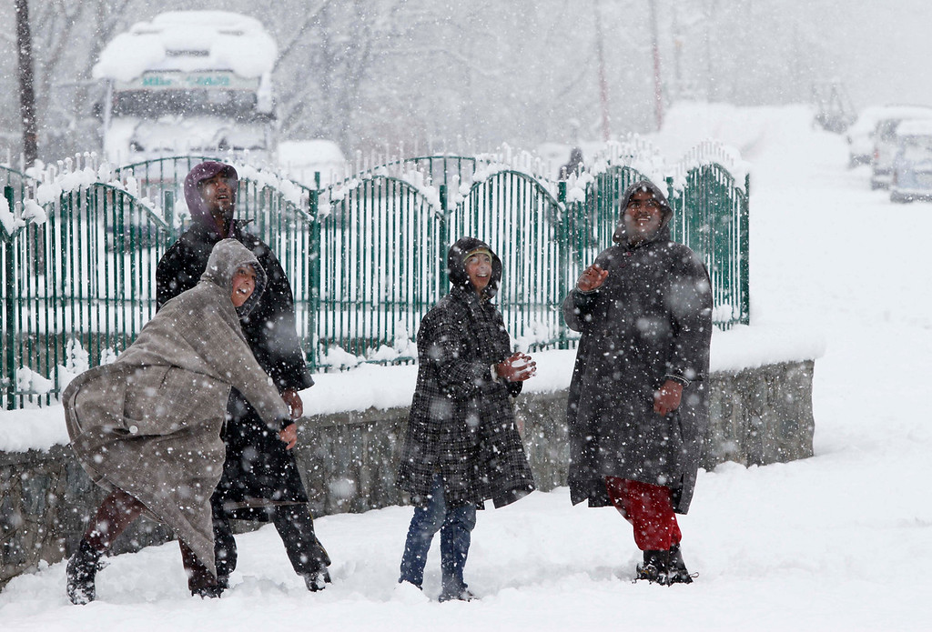 . Kashmiri boys play with snow during snowfalls in Srinagar, India, Tuesday, Dec. 31, 2013. Snowfalls in the Indian portion of Kashmir has disrupted power supply,air traffic and road traffic between Srinagar and Jammu, the summer and winter capitals of India\'s Jammu-Kashmir state, according to news reports. (AP Photo/Mukhtar Khan)