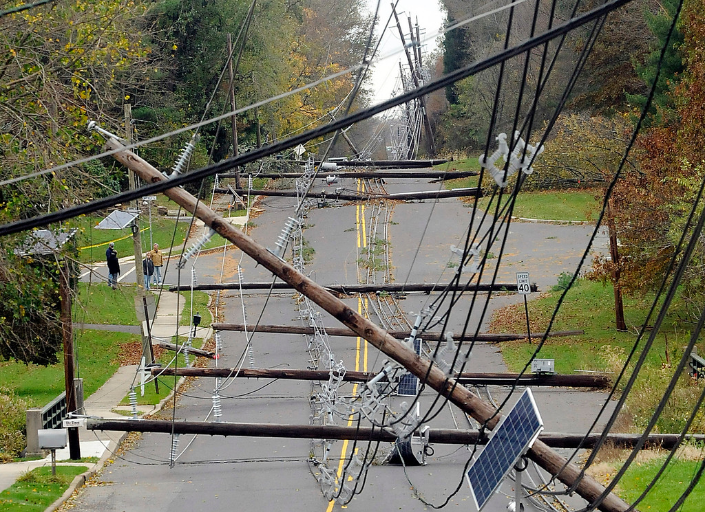 . In this Thursday, Nov. 1, 2012 photo, downed utility poles and wires lie along Bull Run Road in Hopewell Township, N.J, three days after Hurricane Sandy swept through the region, leaving many without power. (AP Photo/The Trentonian, Jackie Schear)