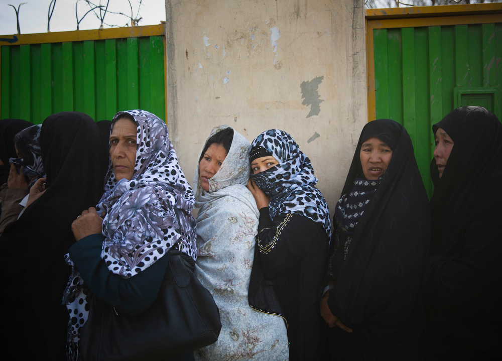 . Afghan women queue outside a school to get their registration card on the last day of voter registration for the upcoming presidential elections outside a school in Kabul, Afghanistan, Tuesday, April 1, 2014. Elections will take place on April 5, 2014. (AP Photo/Anja Niedringhaus)