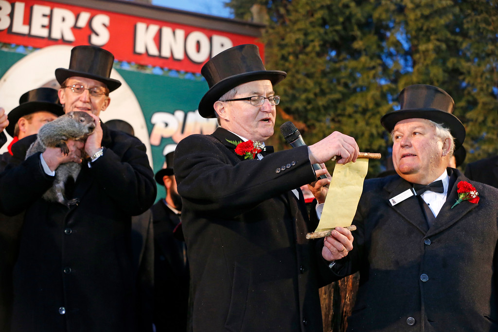 . Punxsutawney Phil is held by Ron Ploucha, left, as Ground Club Vice President Jeff Lundy, center, reads the weather proclamation after Phil saw his shadow and predicted six more weeks of winter weather after, as Ground Club President, Bill Deeley, right,  listens on Gobblers Knob in Punxsutawney, Pa.,  Sunday, Feb. 2, 2014.  (AP Photo/Gene J. Puskar)