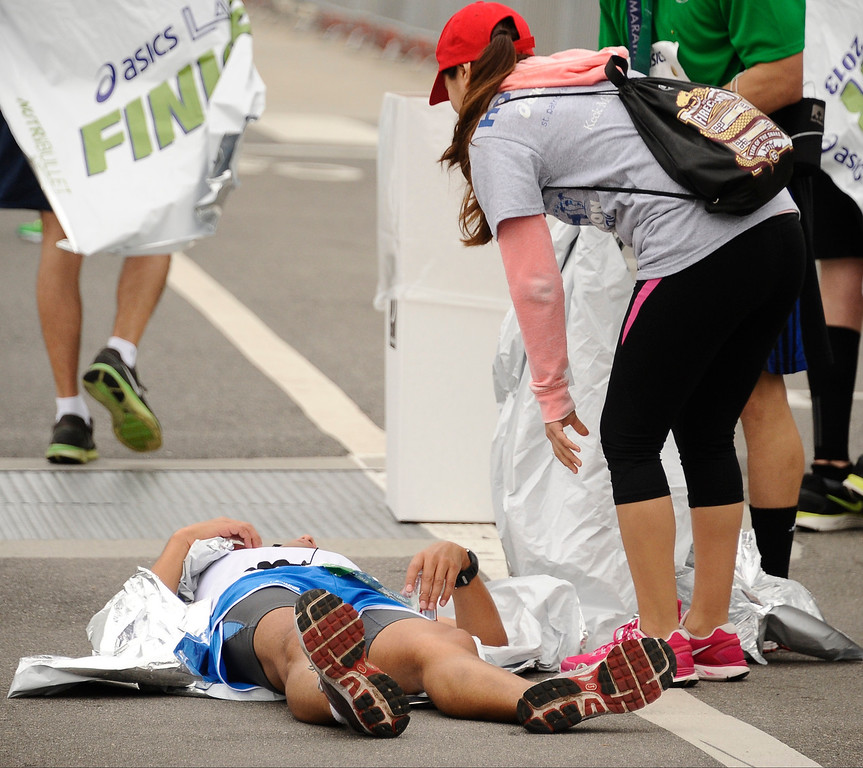 . LA marathon runners feel the pain as the cross the finish line during the 2013 LA Marathon. Santa Monica March 17,2013. Los Angeles Photo by Gene Blevins/LA DailyNews