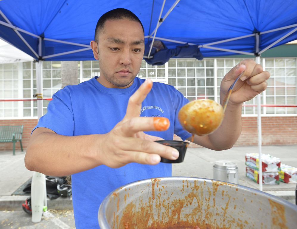. TORRANCE, CALIF. USA -- Fire fighter Marcus Sasaki dishes out chili in Torrance, Calif., on April 14, 2013. The Old Torrance Festival Day is a charity fundraiser that will benefits the South Bay Police and Fire Memorial Foundation and the Torrance Relay for Life. Photo by Jeff Gritchen / Los Angeles Newspaper Group
