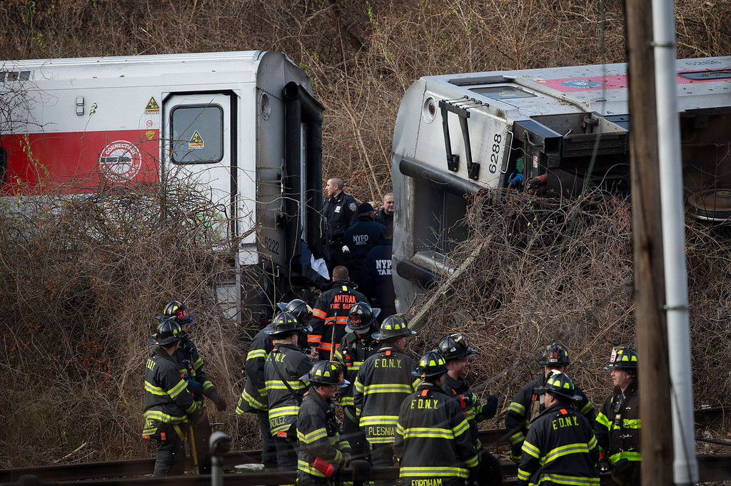 . Emergency personnel gather at the scene of the derailment of a Metro-North passenger train in the Bronx borough of New York Sunday, Dec. 1, 2013.  The train derailed on a curved section of track in the Bronx on Sunday morning, coming to rest just inches from the water and causing multiple fatalities and dozens of injuries, authorities said. Metropolitan Transportation Authority police say the train derailed near the Spuyten Duyvil station. (AP Photo/Craig Ruttle)