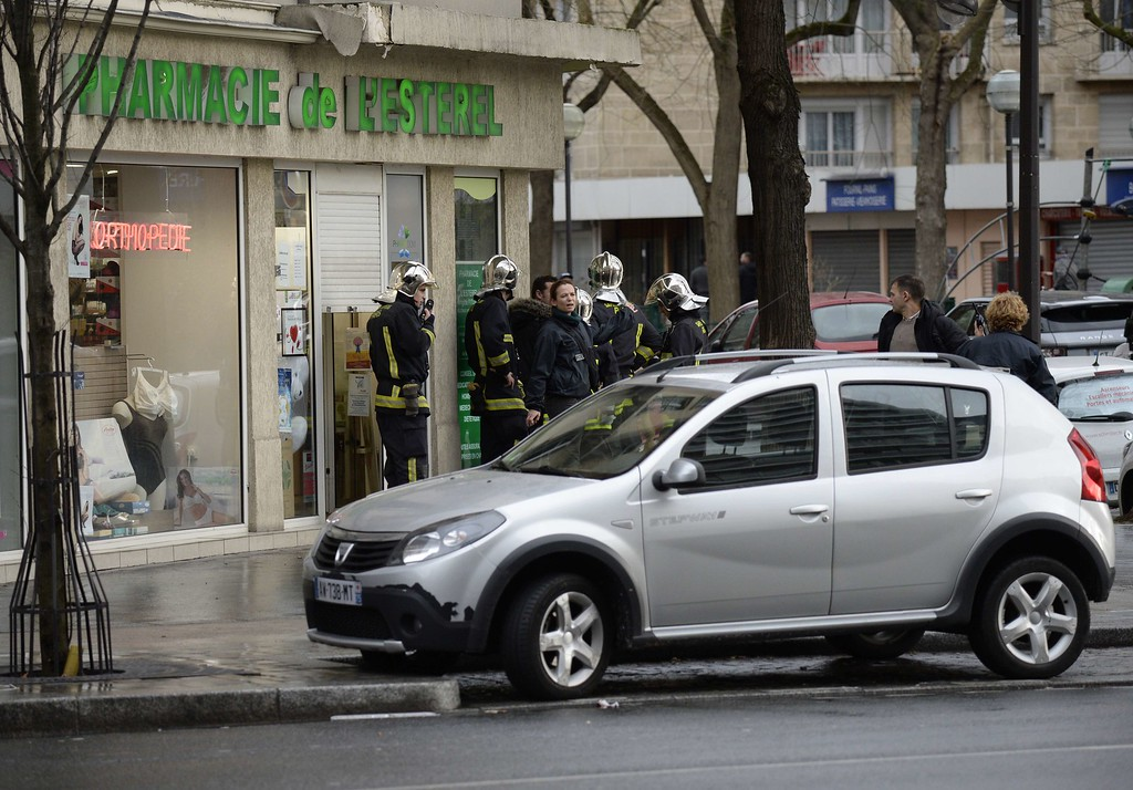 . Firefighters gather by a chemist store at Porte de Vincennes, eastern Paris, after at least one person was injured when a gunman opened fire at a kosher grocery store on January 9, 2015 and took at least five people hostage, sources told AFP. The attacker was suspected of being the same gunman who killed a policewoman in a shooting in Montrouge in southern Paris on January 8.       AFP PHOTO / ERIC  FEFERBERG/AFP/Getty Images