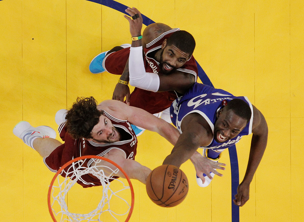 . Cleveland Cavaliers\' Kevin Love, left, battles for a rebound with Golden State Warriors forward Draymond Green, right, and teammate Kyrie Irving, center, during the second half of an NBA basketball game Friday, Dec. 25, 2015, in Oakland, Calif. (AP Photo/Marcio Jose Sanchez)