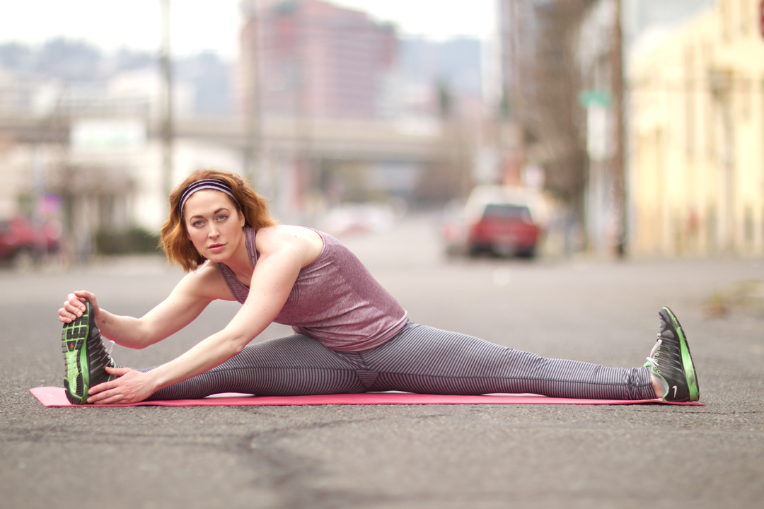 fitness model stretching in the street on a yoga mat