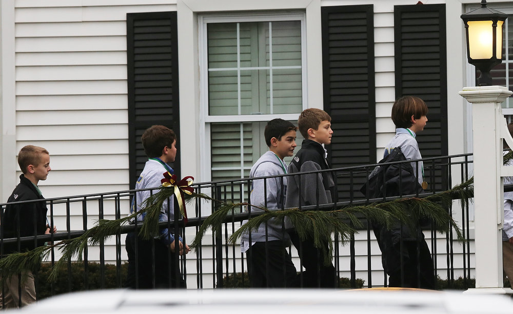 Description of . Boys enter Honan Funeral Home before the funeral for six-year-old Jack Pinto on December 17, 2012 in Newtown Connecticut. Pinto was one of the 20 students killed in the Sandy Hook Elementary School mass shooting.  (Photo by Mario Tama/Getty Images)