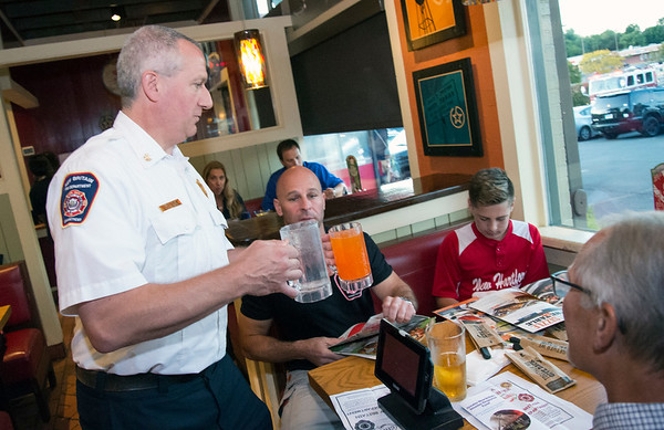 09/25/19 Wesley Bunnell | StaffrrTip a Firefighter took pace at Chili's in New Britain on Wednesday night. The event raised money for the city 's partnership with the community foundation regarding the new disaster relief program. Deputy Chief Michael Berry, brings drinks to a table of customers.