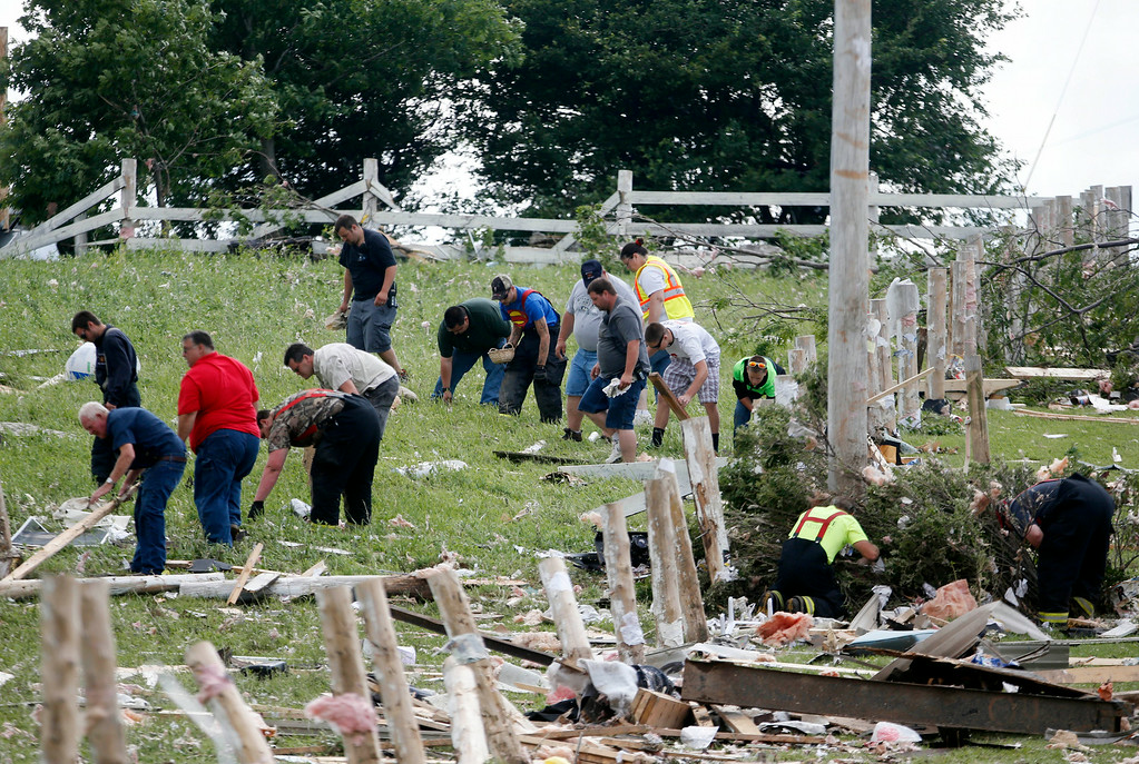 . People sort through debris after Tuesday night\'s storm, on Wednesday, July 9, 2014, in Smithfield, N.Y. (AP Photo/Mike Groll)